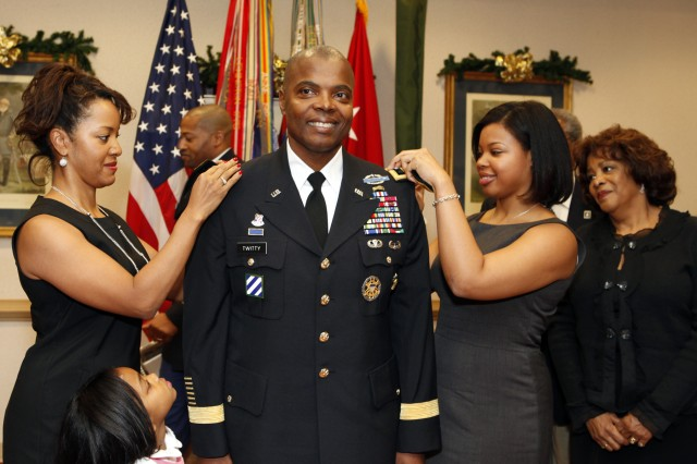 FORT McPHERSON, Ga. (November 30, 2009) - Third Army Chief of Staff Brig. Gen. Stephen M. Twitty receives new shoulder boards reflecting his rank of brigadier general from wife, Karen, (left) and daughter Ashley Twitty during a promotion ceremony Nov. 30 as his mother Belinder, and daughter Brooke, 4, observe. As chief of staff for Third Army, Twitty assists with both the buildup in Afghanistan along with the Responsible Drawdown efforts in Iraq. The command also conducts hundreds of peacetime military engagements annually within the 20-nation U.S. Central Command area of responsibility, which spans from northern African to central Asia and encompasses the Middle East.  (Photo by Cpl. Alex Godinez, Third Army/USARCENT Public Affairs).