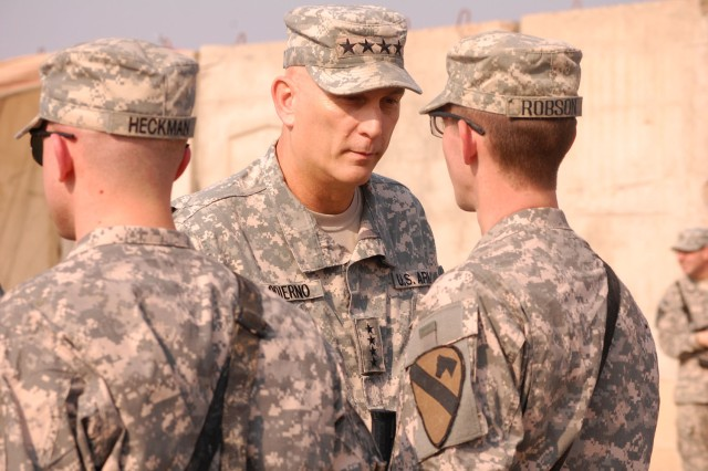 TAJI, Iraq - Gen. Ray Odierno, commander of Multi-National Force-Iraq, hands a challenge coin to Crestview, Fla. native, Pfc. William Robson, an artilleryman assigned to 1st Brigade Combat Team, 1st Cavalry Division, during Odierno's visit to Joint Security Station Sheik Amir, Nov. 26. Odierno traveled to JSS Sheik Amir to visit Soldiers on Thanksgiving Day.