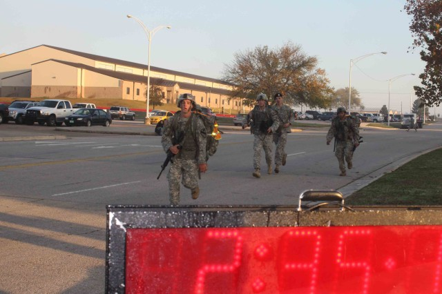 A group of Soldiers, assigned to the 4th Brigade Combat Team, 1st Cavalry Division, run toward the finish line prior to completing a 12-mile road march. The Soldiers earned their Expert Infantry Badge Nov. 23.