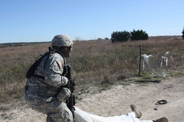 Staff Sgt. Sidney, Lintuan, assigned to Company B, 2nd Battalion, 12th Cavalry Regiment, 4th Brigade Combat Team, 1st Cavalry Division pulls and enemy combatant to safety during Expert Infantry Badge testing Nov. 23. Lintuan was one of 14 Soldiers who earned their Expert Infantry Badge.