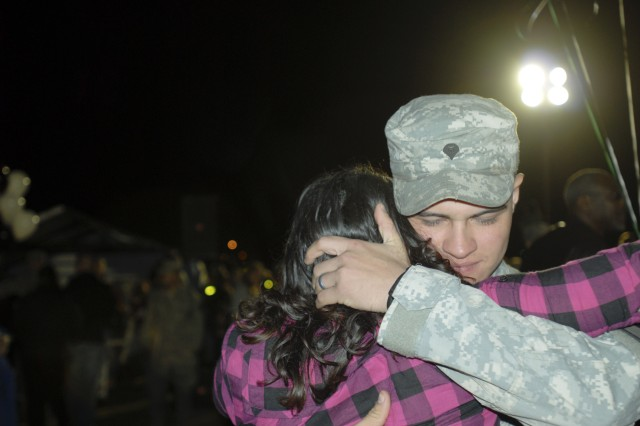 Spc. Andrew Chavez, an infantryman with 3rd Battalion, 8th Cavalry Regiment, 3rd Heavy Brigade Combat Team, 1st Cavalry Division hugs his wife on Cooper Field, in front of the division's headquarters building, upon his unit's redeployment to Fort Hood Nov. 25. The brigade will continue their redeployment from northern Iraq until mid December.