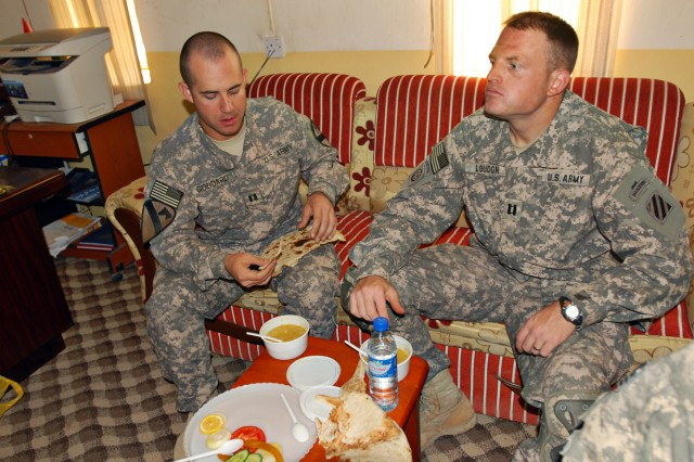 """Capt. Michael Goddard (left), commander of Company E, 1st Battalion, 8th Cavalry Regiment 2nd Brigade Combat Team, 1st Cavalry Division, and Capt. Nick Loudon (right), a company commander with 1st Battalion, 30th Infantry Regiment, 2nd Brigade Combat Team, 3rd Infantry Division, break bread during """"left seat/right seat"""" operations to allow the incoming unit to gain situational awareness of their area of responsibility. Capt. Loudon is set to take over for Capt. Goddard's unit in the next several weeks."""
