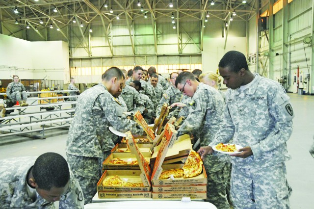 AIT students help themselves to pizza during a Nov. 25 Bible study at Fort Rucker's Yano Hall. The weekly study aids many AIT students in adjusting to life away from home.