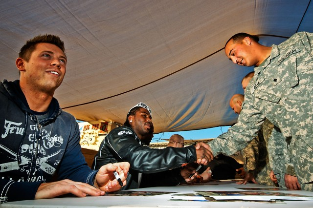 CAMP TAJI, Iraq-World Wrestling Entertainment superstars Mike 'The Miz' Mizanin (left) and JTG (center), sign autographs with Soldiers from the 615th Aviation Support Battalion,1st Air Cavalry Brigade, 1st Cavalry Division, here, Dec. 2, as part of a Morale, Welfare and Recreation sponsored WWE visit.