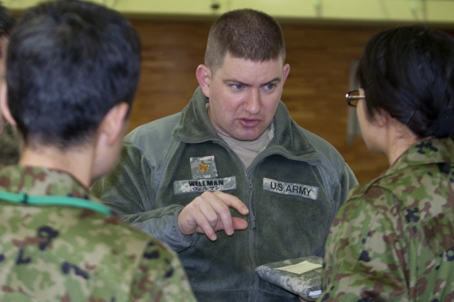 CAMP HIGASHI-CHITOSE, Japan (Dec. 3, 2009) - Maj. Richard Wellman, One Team Joint Task Force signal officer, instructs two language support specialists with the Japan Ground Self-Defense Force on the procedures for accessing the Adobe Connect system during communications set up in the combined operations/information center here during Exercise Yama Sakura 57.  Since its inception in 1982, Yama Sakura has focused on the development and refinement of the JGSDF and U.S. Army, Japan efforts in the areas of bilateral planning, coordination and interoperability through training.  (photo by U.S. Army Sgt. Gerardo DeAvila, 124th Mobile Public Affairs Detachment)