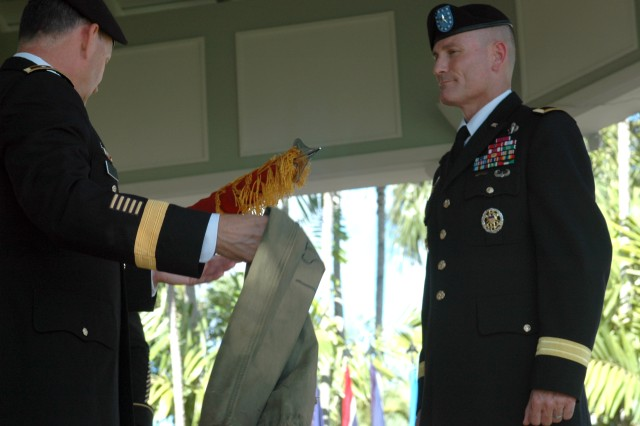 Brig. Gen. Jeffery L. Underhill, commanding general, 94th Army Air and Missile Defense Command looks on as Lt. Gen. Benjamin R. Mixon, commanding general, U.S. Army, Pacific, uncases Underhill's personal flag depicting his rank at Underhill's promotion ceremony here Wednesday.  The flag will remain on display in Underhill's office, or with him at all professional functions.