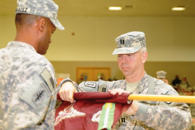 Capt. Stephen R. Spulick, commander of the 8th Medical Logistics Company and a Biddeford, Maine, native, cases the unit flag in a transfer of authority ceremony at Morale, Welfare and Recreation center east Nov. 27 at Joint Base Balad, Iraq