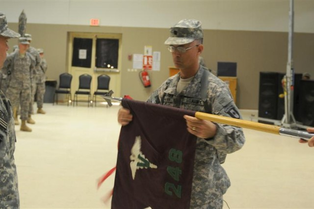 Lt. Col. Kelley A. Mann, commander of the 248th Medical Detachment and an Austell, Ga., native, uncases the unit flag in a transfer of authority ceremony at Morale, Welfare and Recreation center east Nov. 27 at Joint Base Balad, Iraq.