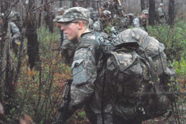 Soldiers take a knee and conduct security while a reconnaissance group moves ahead to ensure their path is clear.