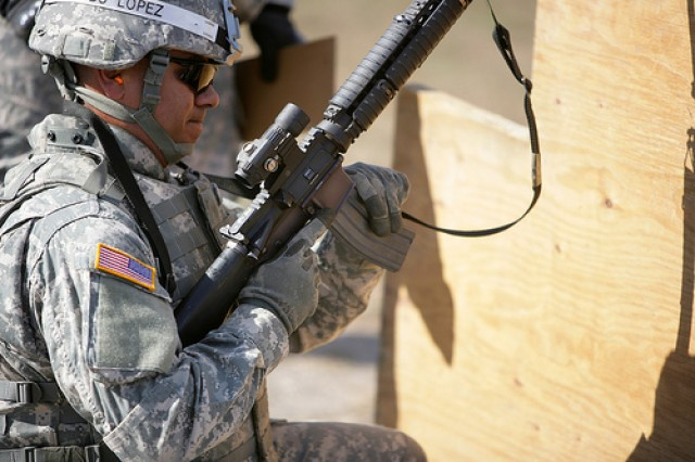Staff Sgt. Miguel Lopez, A Company, 3rd Battalion, 378th Regiment, loads a magazine from behind a barricade during a assault rifle marksmanship scenario in an outcomes-based training and education course. Lopez' expertise showed in the 300-meter three target contest where he twice fired only three shots to hit all three targets.