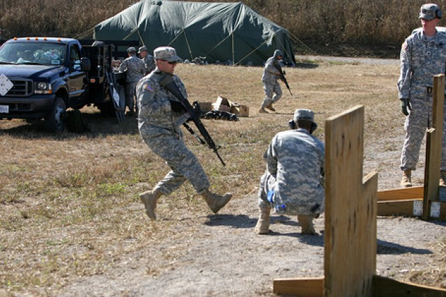Soldiers run up to a barricade while competing in a rifle relay shoot during an outcomes-based training and education course. Rather than a day at the range plugging targets with rifle fire, Soldiers learned skills in the course directly adaptable to combat scenarios.