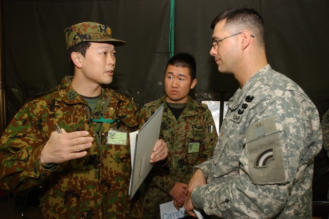 Capt. Satoshi Saitou, fire liason officer of the Japanese Defense Forces 2nd Division (left), 2nd Lieutenant Kennichi Nishino, a 2nd Division interpreter (middle), and Maj. Jamey Barcomb of the 42nd Infantry Division (right) coordinate a meeting between command elements of their divisions. The two divisional headquarters are training together during Yama Sakura 57 at Camp Chitose, Japan Dec. 3-15. Yama Sakura is the annual bilateral command post exercise to train Japanese and U.S. forces for full spectrum operations for Japan's homeland defense.