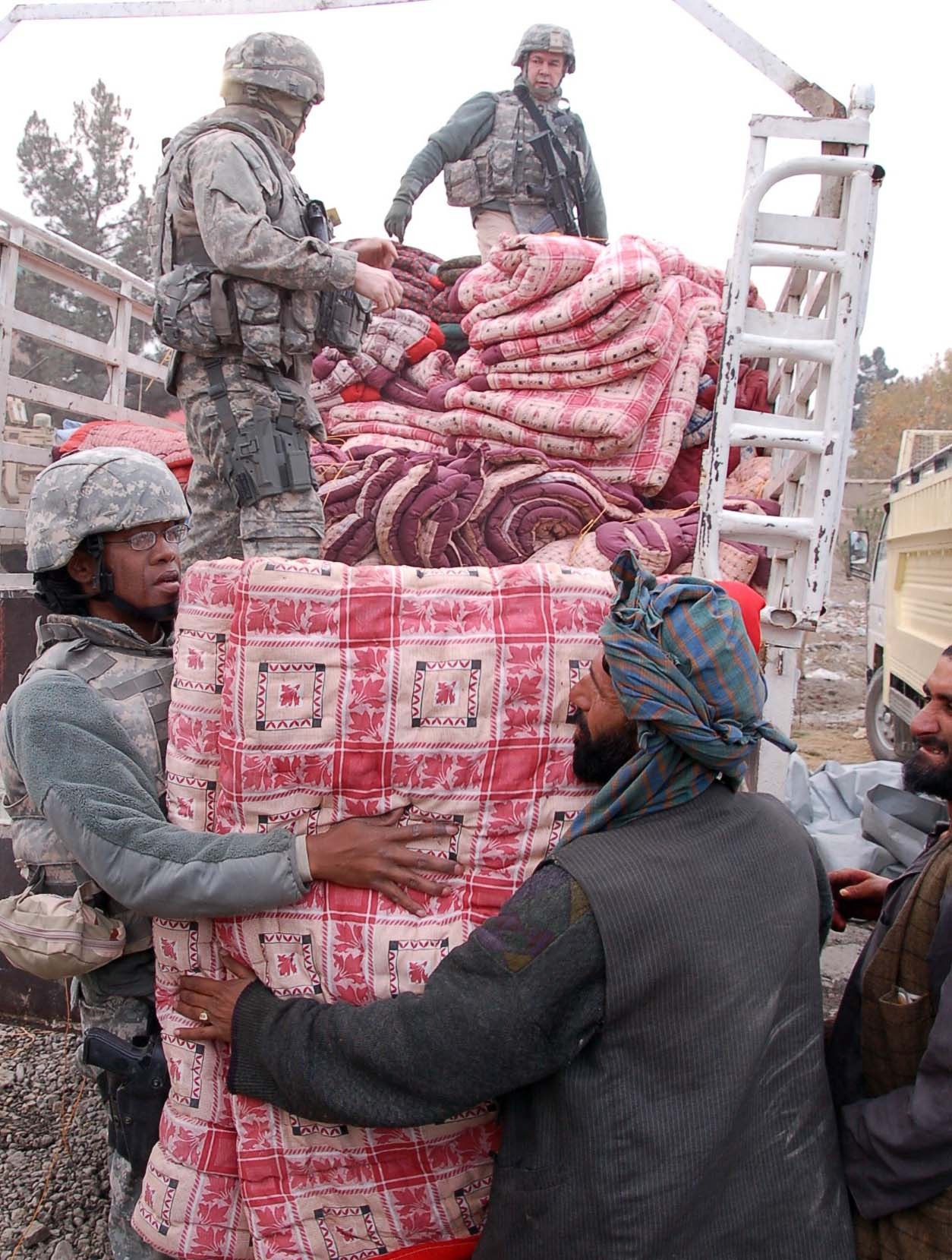 Volunteers distribute blankets to needy Afghan refugee families. The blankets were made by widows of Afghanistan National Police members. The Volunteer Community Relations program purchased them with proceeds from a donation to help the widows with their small business. (USACE photo by Hank Heusinkveld)