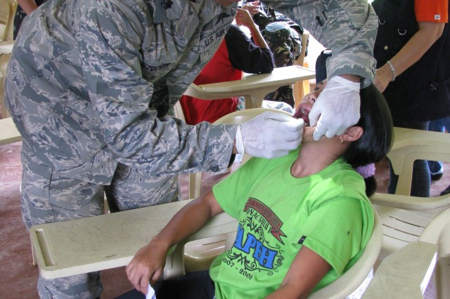 091128-N-1008D-082 JOLO, Philippines (Nov. 28, 2009) U.S. Air Force Lt. Col. Arnold Stocker, a nurse anesthetist assigned to Joint Special Operations Task Force-Philippines, extracts a tooth from a young girl during a Medical Civic Action Project (MEDCAP).  Lead by the Armed Forces of the Philippines, JSOTF-P members assisted with the treatment of more than 200 patients for dental care, medical check-ups, and distributed medications and toiletries. (U.S. Navy photo by Lt.j.g. Theresa Donnelly/Released)