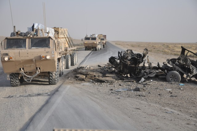 KANDAHAR AIRFIELD, Afghanistan - A U.S. military cargo truck, called a Palletized Load System, bypasses a charred vehicle destroyed by a roadside bomb, while moving building materials Nov. 24 to Forward Operating Base Leatherneck, Helmand province. The 286th Combat Support Sustainment Battalion supports expansion here by running regular convoys to FOBs across Southern Afghanistan. Convoys face multiple dangers from roadside bombs, rocket-propelled grenades, small-arms fire and vehicle-born improvised explosive devices.