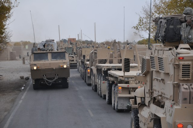 KANDAHAR AIRFIELD, Afghanistan - A U.S. military cargo truck, called a Palletized Load System, laden with building materials passes an empty convoy of PLS trucks and Mine-Resistant, Ambush-Protected vehicles on a mission to Forward Operating Base Leatherneck, Helmand province Nov. 24. The empty convoy was returning after moving expansion resources to FOB Leatherneck. Both convoys were run by the 286th Combat Support Sustainment Battalion.