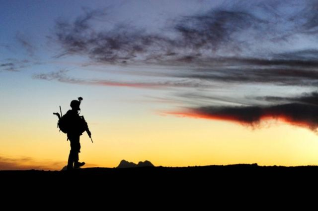 A Soldier stands against the Afghan skyline after securing a combat outpost in Rajankala in the Kandahar province of Afghanistan, Nov. 26, 2009.