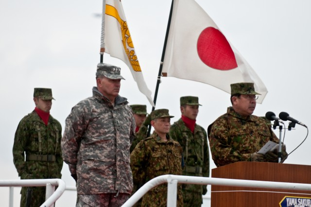 """Lt. Gen. Takeshi Sakai, commanding general, Northern Army, Japan Ground Self-Defense Force, addresses the troops while Lt. Gen. Benjamin R. Mixon, commanding general, United States Army, Pacific, looks on during the opening ceremony for Yama Sakura 57. More than 1,500 U.S. military personnel and nearly 3,500 members of the Japan Ground Self-Defense Force are taking part in the exercise from Dec. 7-13. Yama Sakura, which means """"mountain cherry blossom,"""" is an annual, bilateral exercise designed to strengthen military operations and ties between the U.S. Army and the JGSDF."""