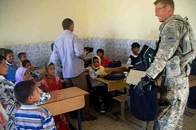Sgt. Kyle Hicks passes out new backpacks and school supplies to the third grade class at Al Diyar School in Muthanna, Iraq, Nov. 1, 2009.