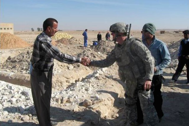 Saleh Mustasher Fahad greets 1st. Lt. Dale Cox at the job site for the Al Salman School in Iraq's Muthanna province, Nov. 1, 2009.