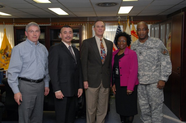 """Col. Larry 'Pepper' Jackson (right), USAG-RC commander and Richard Davis (left), USAG-RC deputy commander, spoke with Leopold Toledo (second from the left), Civilian Human Resources Agency far east regional director, Clifford Dickman (middle), CHRA deputy director, and Geraldine Jones (second from the right), USAG-RC Civilian Personnel Advisory Center director, during Dickman's visit to Area 1 Dec. 7 at the USAG-RC command group building. Dickman spoke after meeting with Jackson about the importance of his visit because """"understanding the commander's intent and understanding what is important to them will help us better plan to meet their requirements and needs."""""""