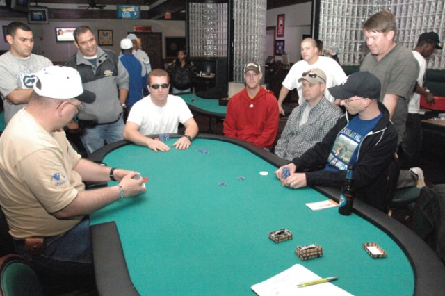 Brian Simecek (end of table) awaits his winning hand of Kings and 8s during the 2009 Texas Hold'em Championship held Nov. 28 in Red Cloud's Mitchell's Club. Adam Pepper (table right holding poker chips) awaits his hand of 10s.