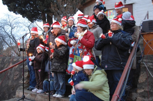 Family members hold vigil candles and sing Christmas carols on the steps of Camp Stanley's Chapel during the Christmas Tree Lighting Ceremony held on Stanley Dec. 8.