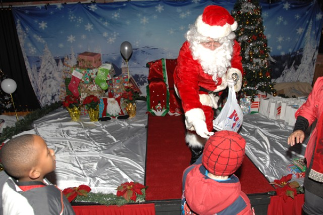 Santa hands gifts of candy and toys to children of Family members during the USAG-Casey Christmas Tree Lighting ceremony Dec. 1.