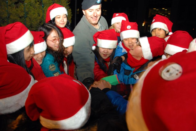Major Gen. Michael S. Tucker (center) 2nd Infantry Division commander, throws the switch with children of Family members on Red Cloud to light up the USAGRed Cloud Christmas Tree Dec. 3.