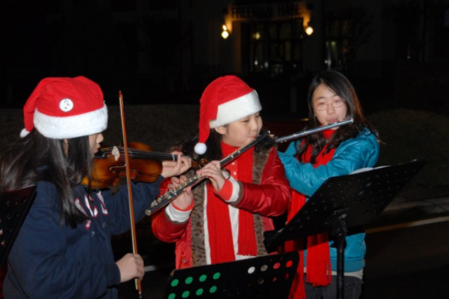 A trio of two flutes and a violin perform for Family members providing holiday music for the USAG-Red Cloud Christmas Tree Lighting ceremony Dec. 3 in front of Freeman Hall on Red Cloud.