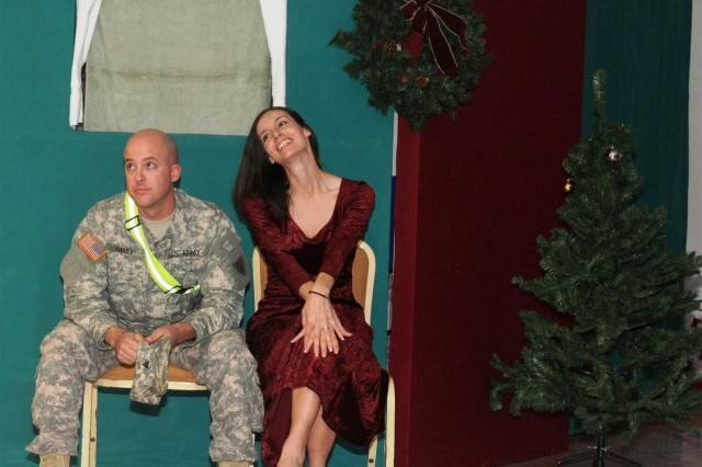 "Sgt. Andrew J. Schneiders, command executive assistant with Task Force 38 and a Mooresville, Ind., native, and Capt. Christina Shepard, logistics officer with TF 38 and Clayton, Ind., native, act out a scene in the military version of ""It's a Wonderful Life,"" titled ""It's a Wonderful Deployment."""