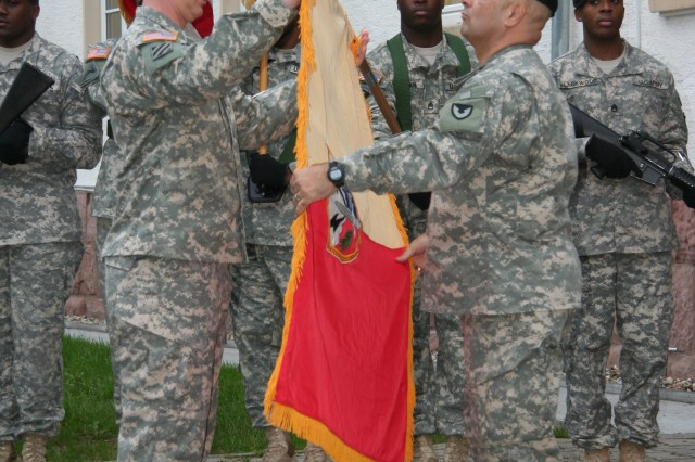 Col. Jack Haley (left), commander of the 405th Army Field Support Brigade, and Command Sgt. Maj. Ismael Rodriguez, the 405th AFSB command sergeant major, unfurl the 405th AFSB's colors as part of the brigade's official relocation to