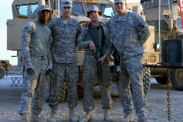 CONTINGENCY OPERATING LOCATION Q-WEST, Iraq - The battalion commander poses with his gun truck crew. Lt. Col. Kerry Goodman (second from left), a Meridian native commanding 2nd Battalion, 198th Combined Arms out of Senatobia, Miss., stands with Pfc. Derrell A. Pittman (left), a driver from Greenville, Miss., Pfc. William C. Williamson (third from left), a turret gunner from Seattle, Wash., and Sgt. John F. Diviney, a vehicle noncommissioned officer in charge from Spokane, Wash. Goodman accompanied Soldiers of B Company, 2/198th CAB, out of Greenwood, Miss., on a convoy security mission from Contingency Operating Location Q-West to Forward Operating Base Warrior Nov. 24 and 25.