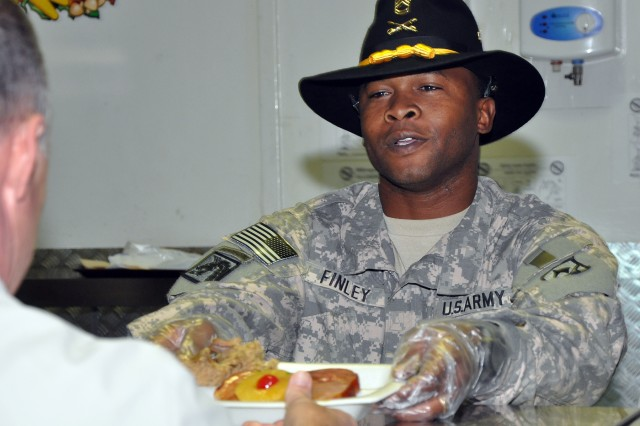 Sgt. 1st Class Aaron Finley, 15th Sustainment Brigade schools and training noncommissioned officer, serves Thanksgiving dinner in the dining facility here, Nov. 26. It is traditional for senior noncommissioned officers and commissioned officers to serve their subordinates Thanksgiving dinner. (U.S. Army photo by Sgt. Matthew C. Cooley, 15th Sustainment Brigade public affairs)