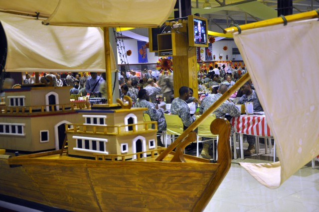 Thousands of Soldiers eat Thanksgiving dinner at the dining facility here, Nov.26, surrounded by decorations including a large model of pilgrim's ship. (U.S. Army photo by Sgt. Matthew C. Cooley, 15th Sustainment Brigade public affairs)