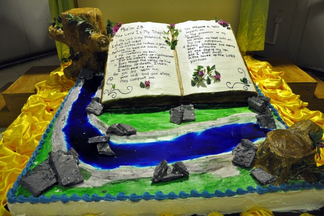 A 3-D cake made by Sixto Jimenez, a San Jose Del Monte, Philippines, native and head baker for the dining facility here, sits on display at Thanksgiving dinner next to a dining facility entrance here, Nov. 26, showing a Bible open to the 23rd Psalm. (U.S. Army photo by Sgt. Matthew C. Cooley, 15th Sustainment Brigade public affairs)