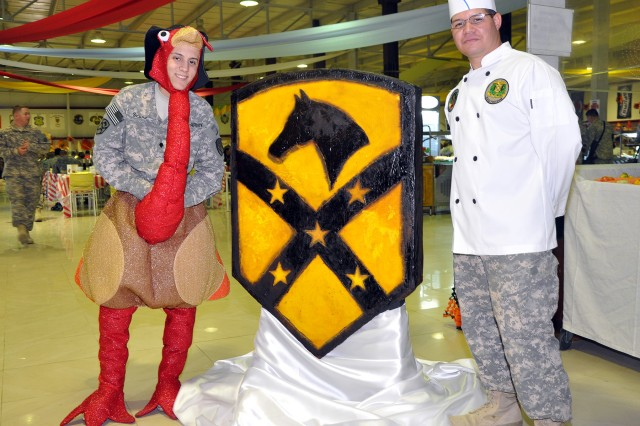 "Spc. Carlos Seijo [left], a 15th Sust. Bde. cook, dresses like a turkey while Pfc. Daniel Rivera, also a 15th cook, stands by the hardened sugar ""Wagonmaster"" patch he created during a Thanksgiving feast here, Nov. 26. (U.S. Army photo by Sgt. Matthew C. Cooley, 15th Sustainment Brigade public affairs)"