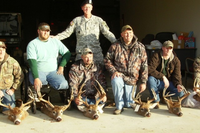 Sgt. Maj. Paul Baxter, depot military affairs, stands with wounded warriors who participated in one of two deer hunts on Blue Grass Army Depot.