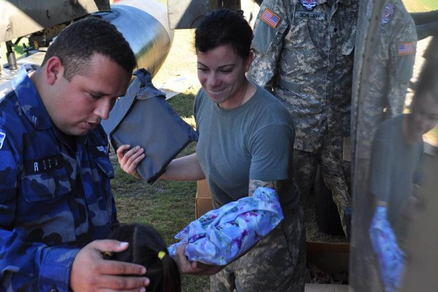 Sgt. Elena Clark, a flight medic assigned to Joint Task Force-Bravo, hands a bag full of school supplies to a little girl Nov. 22, near Las Isletas, El Salvador. The JTF-Bravo Medical Element performed a Medical Civil Action Program, or MEDCAP, from Nov. 19 to 23 treating 2,987 people in several different cities affected by the El Salvador mudslides.