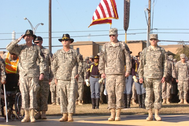 Col. Gary Volesky, commander of 3rd Heavy Brigade Combat Team, 1st Cavalry Division, salutes as he reports to the Rear-Detachment commander, as the brigade's Command Sgt. Maj. James Pippen, 1st Battalion, 12th Cavalry Regiment, commander, Lt. Col. Michael Fadden and 1-12, Command Sgt. Maj. Eddie Del Valle, stands at attention during 3rd HBCT's homecoming at Cooper Field at the division headquarters, Dec. 3, at Fort Hood, Texas. The brigade completed a 12-month deployment in northern Iraq, where they successfully withdrew from the inter-city of Mosul.