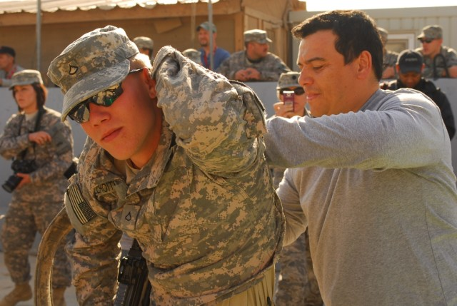 A Soldier with 1st Battalion, 8th Cavalry Regiment, 2nd Brigade Combat Team, 1st Cavalry Division, has his shirt signed by comedian Carlos Mencia at Joint Security Station McHenry in Kirkuk province, Iraq, Dec. 2. Mencia, and singers Kid Rock and Jes...
