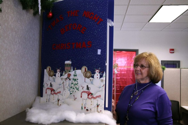 """Brenda Turner, U.S. Army Space and Missile Defense Command/Army Forces Strategic Command G2, looks at Theresa Morris' oversized copy of """"The Night Before Christmas"""" on display in the G2 office."""