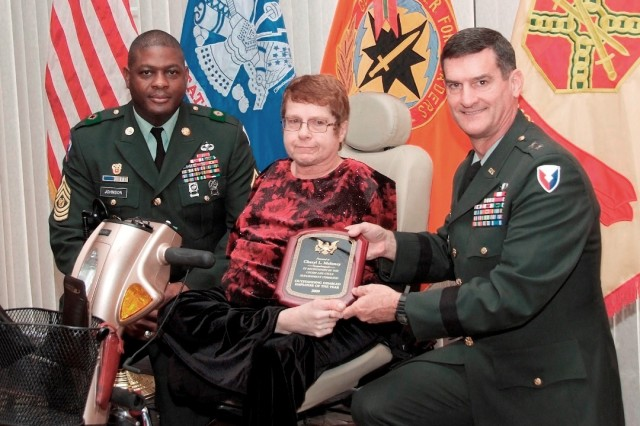 Command Sgt. Maj. Tyrone Johnson and Maj. Gen. Randolph P. Strong present a plaque to Cheryl Maloney in recognition of her selection as the CECOM LCMC Disabilities Employee of the Year during the 26th Annual Disabilities Awards luncheon at Gibbs Hall on Nov. 5.