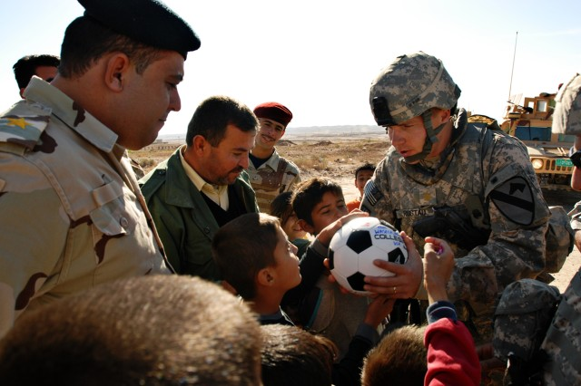 """Major Tim Rustad, a Mankato, Minn., native and in charge of the 49th Iraqi Army Brigade Military Transition Team, hands a soccer ball to an Iraqi child near Dibbis in Kirkuk province Iraq, Dec. 3. Soldiers from the MITT began a soccer ball drive dubbed """"Operation Wild Balls."""" The soccer-balls were donated from friends, Families and others through a Web site set up by the MITT."""