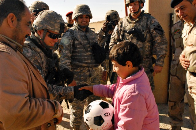 """Team, shakes hands with an Iraqi child after handing him a soccer ball near Dibbis in Kirkuk province Iraq, Dec. 3. Soldiers from the MiTT began a soccer-ball drive dubbed """"Operation Wild Balls"""". The soccer-balls were donated from friends, Families and others through a Web site set up by the MiTT."""