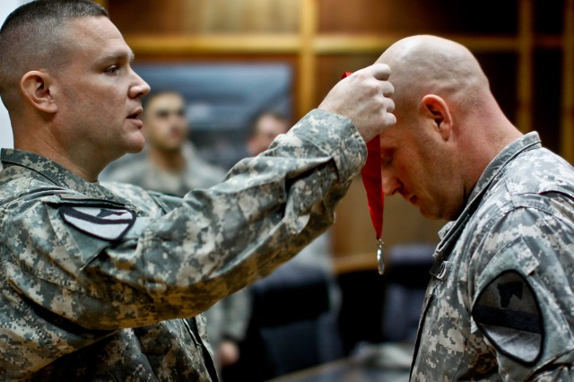 CAMP TAJI, Iraq - Sgt. 1st Class Jeremy Weisheit (right), from Tuscon, Ariz., the fire support noncommisioned officer in charge in 1st Air Cavalry Brigade, 1st Cavalry Division, bows his head to receive The Honorable Order of Saint Barbara award presented to him by Lt. Col. William Smith (left), from Harker Heights, Texas, the deputy fire support coordinater in Company A, Division Special Troops Battalion, 1st Cav. Div., here, Dec. 5.