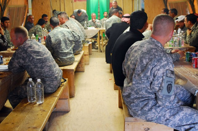The leaders of 1st Brigade Combat Team, 1st Armored Division, and 2nd Brigade Combat Team, 1st Calvary Division, share dinner with leaders from the Sons of Iraq at Joint Security Station McHenry in Kirkuk province, Iraq, Dec. 4.