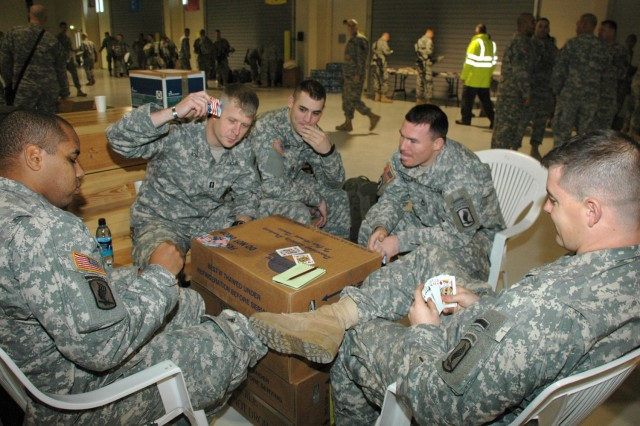 Soldiers of the Vicenza, Italy-based 173rd Airborne Brigade Combat Team play cards while waiting to board an aircraft to deploy to Afghanistan Dec. 9 at Aviano Air Base in Aviano, Italy.  The 700-plus troops waited in the state-of-the-art personnel alert holding area, an Army-managed facilty at the air base.  Servicemembers can watch TV, nap or get a bite to eat in the temperature-controlled facilty while waiting for aircraft.