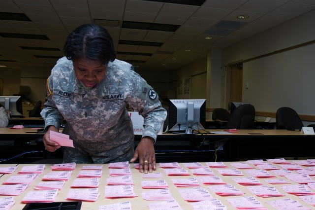 Chief Warrant Officer Ruth Alleyne, a human resources technician assigned to the 81st Regional Support Command's officer branch, places the secret voting sheets during the lieutenant colonel command selection board held Dec. 6 - 9 at Fort Jackson,