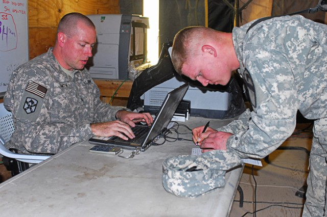 Sergeant Philip Smith, a financial management support team non-commissioned officer in-charge with Charlie Detachment, 24th Finance Company, types up financial information as a Soldier fills out paperwork to receive cash at Joint Security Station McHenry in Kirkuk Province, Iraq, Dec. 4.